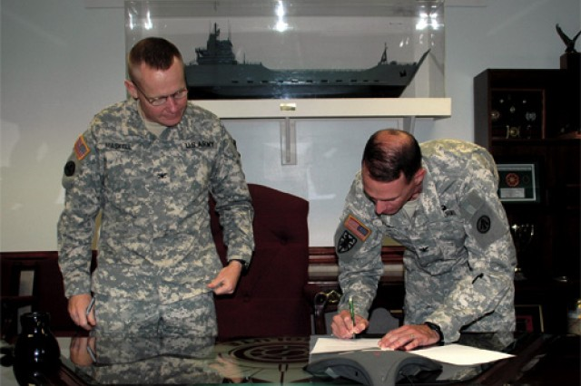 Col. Charles Maskell, 7th Sustainment Brigade commander, looks on as Col. Craig Hymes, 597th Transportation Terminal Group commander, signs the declaration that moved the 688th and 689th Rapid Port Opening Elements from the 7th Sust. Bde.  to the 597th TTG.