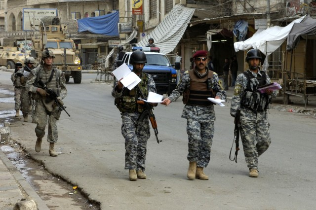 """An officer with the Iraqi National Police distributes information and maps of the areas his """"shurta,"""" or police officers are to cover and clear during Warhorse Scimitar, a sweep, clear and census operation in west Mosul, Iraq on April 23."""