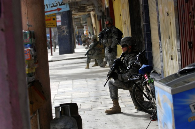 """Soldiers from 2nd Platoon, B """"Bulldog"""" Company, 3rd """"Warhorse"""" Battalion, 8th Cavalry Regiment, 3rd Heavy """"Greywolf"""" Brigade Combat Team, 1st Cavalry Division provide rear security as teams of Iraqi National Police and their fellow Bulldog Soldiers clear buildings throughout Old Town, a neighborhood in west Mosul on April 23."""