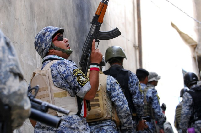 An Iraqi National Police officer checks rooftops and windows for possible hostiles during Operation Warhorse Scimitar on April 23.