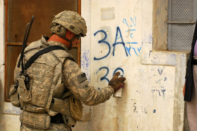 """A Soldier with 3rd Battalion, 8th Cavalry Regiment, 3rd Heavy Brigade Combat Team, 1st Cavalry Division marks a building in """"old town"""" Mosul as cleared by his team consisting of both Coalition and Iraqi forces on April 23."""