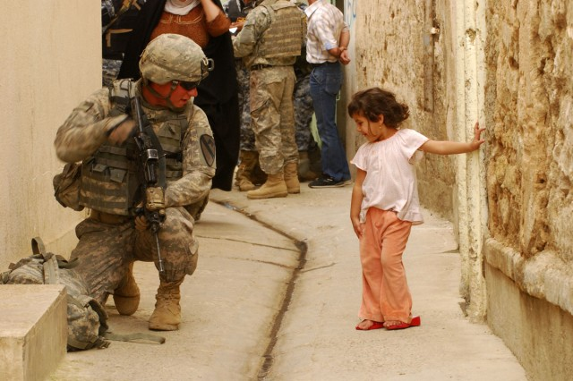 A Soldier with 3rd Battalion, 8th Cavalry Regiment, 3rd Heavy Brigade Combat Team, 1st Cavalry Division demonstrates to an Iraqi child how to properly take a knee on April 23 during Operation Warhorse Scimitar in west Mosul. The child was running up and down this alley way giving high fives to Soldiers.