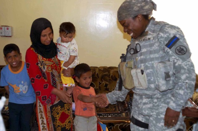 """Demetria Franklin, a police officer from Sugar Land, Texas gives a boy in the western Mosul neighborhood of Al Rabin """"some skin"""" after giving he and his family an assortment of school supplies and accessories. Franklin and the 302nd Military Police Company, 607th Military Police Battalion, 11th Military Police Brigade have been working with the Al Rabin Iraqi Police District Station in an effort to kindle feelings of trust and confidence between the IP and the communities in which they work. The IP are using the same methods as the awareness program D.A.R.E. in the U.S. does."""