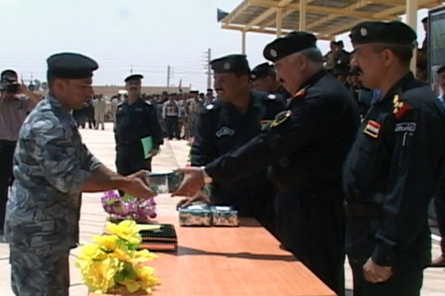 A graduate of the Iraqi Police basic training program receives a gift from the Ninewah General Director of Police, Khalid Hussein Ali al-Hamdani for a job well done during his training cycle on May 15. This graduation marks the last class to graduate, fullfilling the requirement set by the Iraqi Ministry of Interior to have Iraqi Police that are currently working to receive formal basic training.