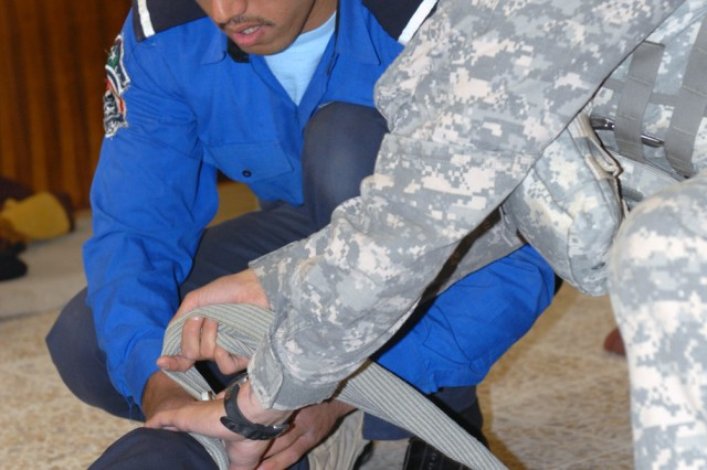 TAJI, Iraq -Pfc. Evan Mead, from Londonderry, N.H., a medic assigned to 591st Military Police Company, 93rd MP Battalion, 8th MP Brigade, assists an Iraqi Policeman with the proper application of an Emergency Trauma Dressing at Tarmiyah Police Station here, May 16. The 591st MPs gave a class in first aid to the Iraqis during a visit the station.
