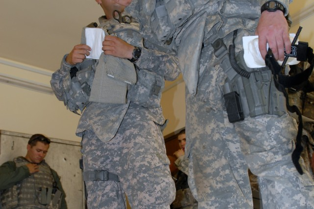 TAJI, Iraq - Pfc. Andrew Van Cleave (right), from Junction City, Kan., assigned to 591st Military Police Company, 93rd MP Battalion, 8th MP Brigade, talks about the Emergency Trauma Dressing at a first-aid class at the Tarmiyah Police Station here, May 16. Iraqi Police were taught how to control bleeding of an extremity, using a tourniquet and bandages.
