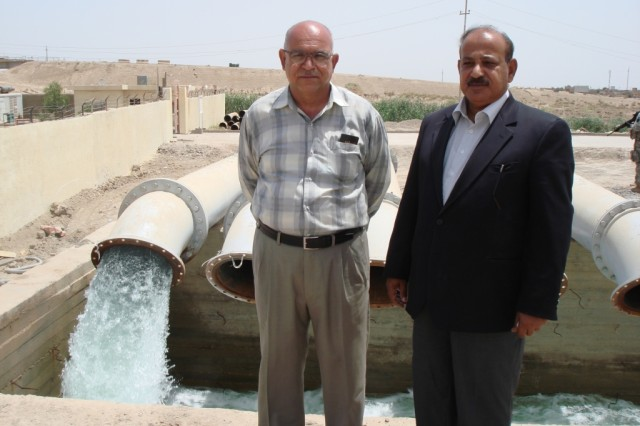 TAJI, Iraq - Engineer Hameed Ibrahim (left), and Directorate General Thair Dahri, both of the Baghdad Water Resources Directorate, stand in front of the irrigation outlet for Pump Station One in Saab Al Bour, Iraq, during a  May 16 visit to the pump station.
