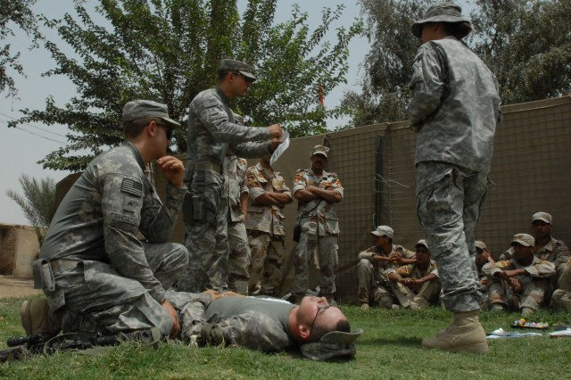 BAGHDAD- Using an interpreter (at right), medic Staff Sgt. Jose Martinez (center standing) of Lebanon, Pa., explains the care of a chest wound to Iraqi Army Soldiers May 17. Martinez used Spc. Dean Matthews (reclined) of Milton, Fla. and Cpl. Jason Rhoads (at left) of Oley, Pa. to demonstrate the technique. The Pennsylvania Army National Guard Soldiers are from 2nd Battalion, 112th Infantry, 56th Stryker Brigade Combat Team.