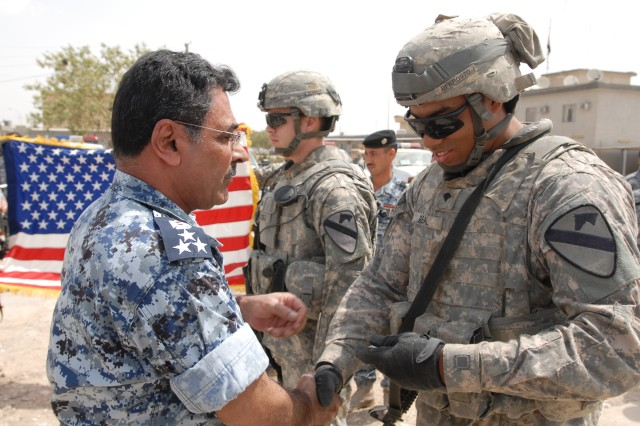 Brig. Gen. Khatad (left), the Iraqi Emergency Services Unit chief, gives Spc. Jonathan Real (right), a Bayamon, Puerto Rico, native and an artilleryman with Battery B, 3rd Battalion, 82nd Field Artillery Regiment, 2nd Brigade Combat Team, 1st Cavalry Division, a coin after his reenlistment ceremony at the ESU Station in Kirkuk city May 11.