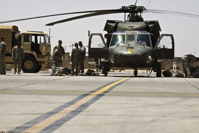 CAMP TAJI, Iraq-An aircrew of a UH-60 Black Hawk helicopter, from 3rd Assault Helicopter Battalion, 227th Aviation Regiment, 1st Air Cavalry Brigade, 1st Cavalry Division, Multi-National Division-Baghdad, unload their gear after touching down on Camp Taji, Iraq, May 18.  The Black Hawk was one of the first aircraft from the 1st Air Cav. Bde., to land in Iraq for the year long deployment