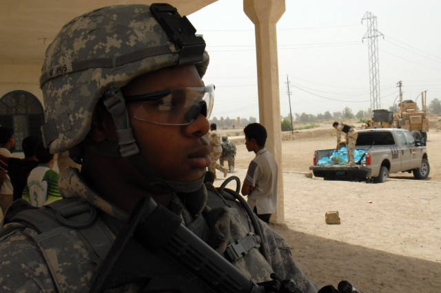 BAGHDAD - Spc. Salon Mohamed of New Orleans, assigned to Co. A, 2nd Bn., 8th Cav. Regt.,  guards a school in the village of Firra Shia while an Iraqi Army officer (background) prepares to distribute a truckload of food bags for needy Iraqis.