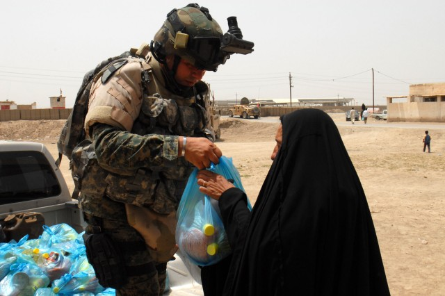 """BAGHDAD - An Iraqi Soldier based at Joint Security Station Aqur Quf hands out a bag of food to an Iraqi woman at a school in the village of Firra Shia west of Baghdad. """"I think it's important for the community to see that the IA and the government of Iraq care just as much about them as we do,"""" said 1st Lt. Michael Neel of Glendale, Calif., an armor officer assigned to Co. A, 2nd Bn., 8th Cav. Regt."""