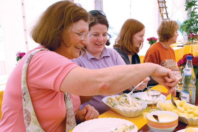 U.S. military spouses enjoy a German traditional meal of Schnitzel, Spargel and new potatoes after working hard in the fields harvesting the white asparagus.