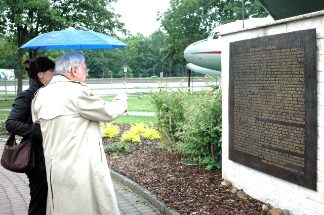 """Attendees at the Berlin Airlift commemoration at the former Rhein-Main Airbase read a plaque dedicated to those who lost their lives during the massive humanitarian effort."""""""