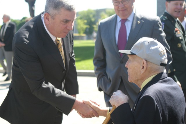 Retired Gen. John Abizaid, class of 1973, shakes the hand of the oldest graduate, 99-year-old retired Col. William H. Waugh Jr. (class of 1934), before alumni ceremonies.