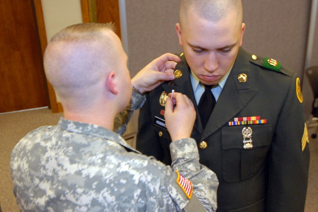 Sponsor Staff Sgt. Joshua Altice, Combined Arms Center and Fort Leavenworth 2008 NCO of the Year, polishes and inspects Fort Leavenworth NCO of the Year competitor Sgt. Robert Hoogerhyde's uniform before his knowledge assessment board May 13 outside the Armed Forces Insurance conference room.