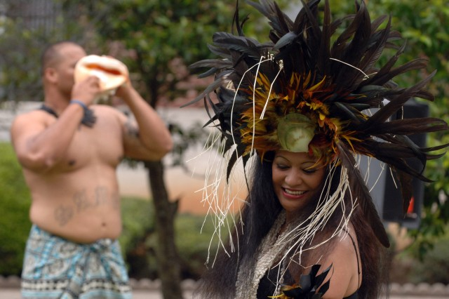"""Semeatu, left, blows a conch shell as Torres, dressed in a traditional Tahitian """"Otea"""" costume, performs a Polynesian dance."""