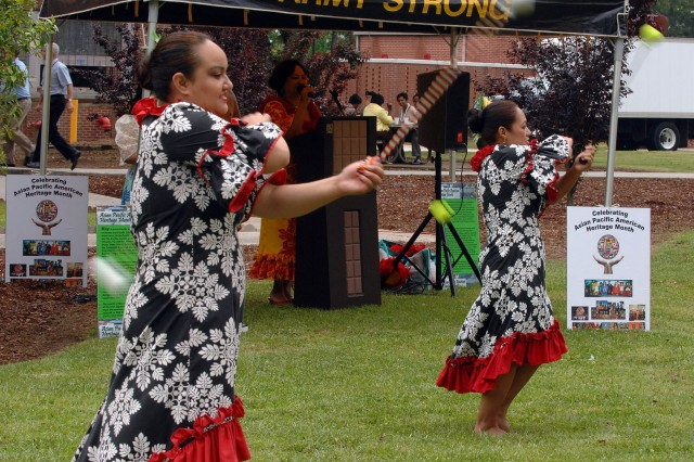 """Lillian Hula Mageo, left, and Torres perform a traditional New Zealand """"Poi Ball"""" dance. As explained by hostess Lehua Kalili, the dance involves rhythmic movements while swinging the poi balls in various figure 8s and arm crosses, as shown."""