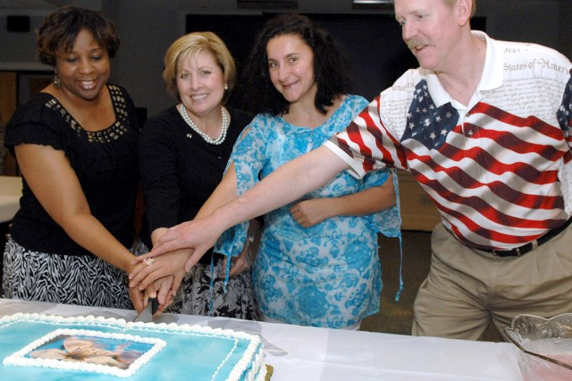 Mary Miller, second from left, wife of the First Army commanding general, Lt. Gen. Thomas G. Miller, gets help cutting the Spouse's Appreciation Day Cake May 8 at First Army headquarters.  Joining are, from left, Marilyn Walker, wife of Maj. Mack Walker, an action officer with G-5, Plans; Yasmin Helal-Barber, wife of Maj. James Barber, an action officer with G-7, Aviation; and Daniel Swacina, husband of Col. Kathleen Swacina, the G-6.