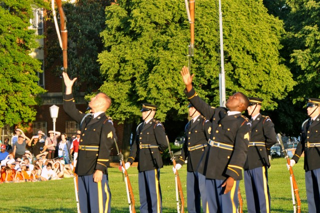 Soloists with the Army Drill Team exhibit advanced skills with the 1903-A3 Springfield Rifle as other members of the elite unit stand ready to resume their silent routine, a staple for appreciative audiences since 1957.
