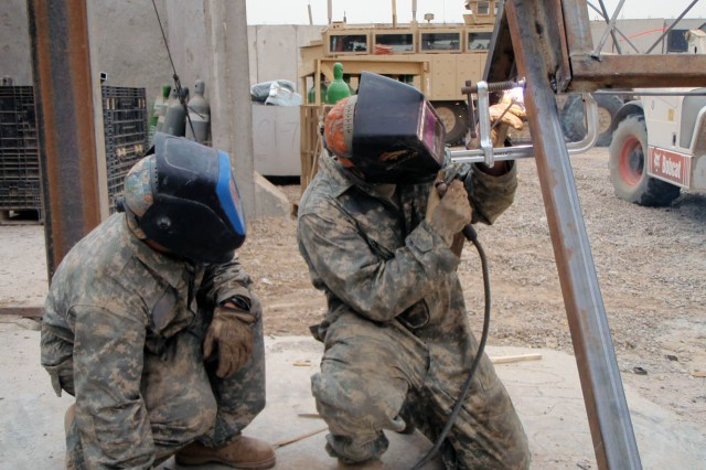 BAGHDAD-Honolulu, Hawaii native, Spc. Antonio (left) and Globe, Ariz. native, Sgt. Nathan Henderson, of Troop D, 1st Squadron, 7th Cavalry Regiment, 1st Brigade Combat Team, 1st Cavalry Division, complete an existing communications tower project in Istiqlaal May 14.  The welders often repair vehicles, but also build or repair other equipment requested through work orders.