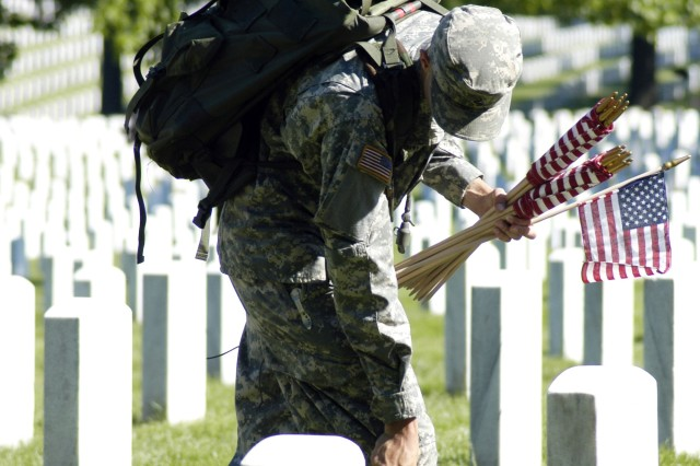 "A Soldier in the 3rd U.S. Infantry Regiment (The Old Guard) measures one foot with his boot, and places a flag in front of a grave marker at Arlington National Cemetery during the annual tradition ""Flags In"" May 21."