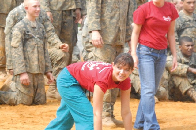 Jessica Scott, left, prepares to run through a Sand Hill obstacle course as Carlie Yarbrough and Soldiers from 1st Battalion, 19th Infantry Regiment, watch.  Scott and Yarbrough were two of more than 40 Miss Georgia contestants who participated in A Salute to Our Troops, a program that gives pageant contestants a closer look at the day-to-day tasks of service members.