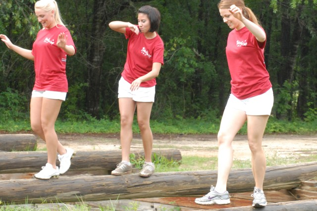 Channing Wood, left, Courtney Piedrahita and Rachel Evans balance on a log obstacle Saturday on Sand Hill as part of their visit to Fort Benning for A Salute to Our Troops.