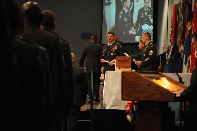 Lt. Gen. William B. Caldwell IV, commanding general Combined Arms Center and Fort Leavenworth, waits for the next member of Class 59 to come up on stage to receive his diploma. Caldwell spoke to the more than 2,000 in attendance, May 21, at the graduation ceremony of Class 59 of the U.S. Army Sergeants Major Academy. Caldwell began his speech by first thanking the many family members in attendance for their support of their graduate during the nine months of instruction.