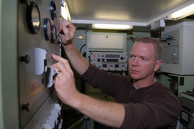 Dave Walsh, electronics worker, operates the power control panel in the AN/TRC-190 shelter during an operational check.