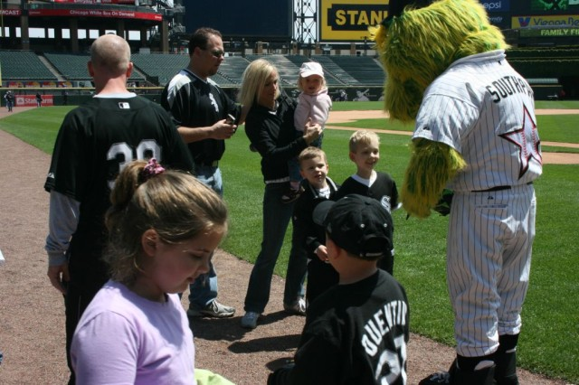 """Family members of deployed Illinois Army National Guard Soldiers were greeted by the Chicago White Sox Mascot, """"Southpaw,"""" after a live Webcast with Afghanistan. The Webcast, Sponsored by 'We Do Care,' and hosted by the 'U.S. Cellular Corporation,' home of the Chicago White Sox, allowed the family members to interact with community leaders and address any concerns. After the broadcast, families were able to enjoy the entire on-field experience with a tour of the field, stadium and dug-outs, at the generosity of the CWS."""