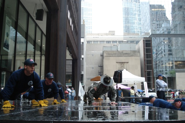 Drill Sergeant Jeremy S. Beals, Drill Sergeant Exhibitor Program, Accessions Support Brigade, Ft. Knox, KY, demonstrates the proper technique for push-ups for his on-stage demonstration of Army physical fitness exercises, during the 'Chicago Moves Day' event downtown on Daley Plaza.  On stage with Beals are recruits from the Chicago Fire Department Academy.  Despite the rain and cold weather in the Windy City, hundreds of people showed up to participate in the event sponsored by the 'Mayor's Fitness Council.'  The Chicago Police Department and the USMC participated as well as other local fitness groups.