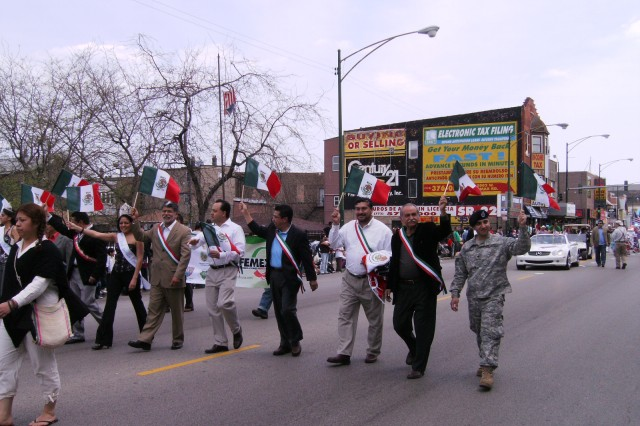 "Sergeant Oscar Gutierrez, 5th/94th Battalion, USAR, waves to the crowd in the ""Cinco De Mayo"" Parade, on Sunday, 03 May, 2009, with Co-Grand Marshall\'s, 12th Ward Alderman, George Cardenas; 25th Ward Alderman, Daniel Solis; ""Miss Cinco De Mayo;"" and others, as they march down West Cermak Road, in the Pilsen neighborhood of downtown Chicago, to a crowd of several thousand."