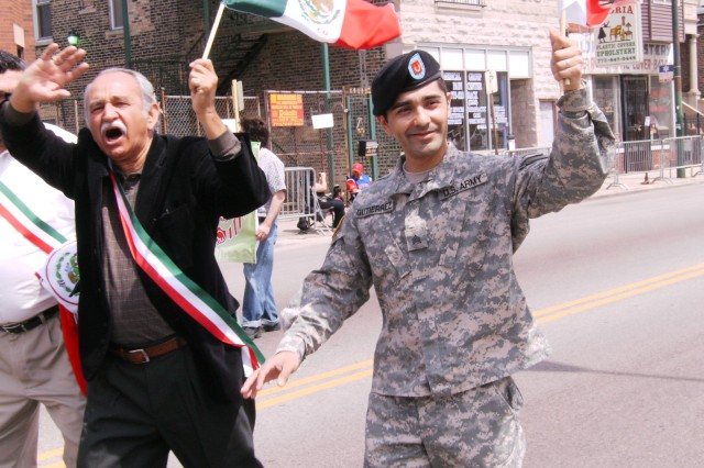 "Sergeant Oscar Gutierrez, 5th/94th Battalion, USAR, waves to the crowd with, 25th Ward Alderman, Daniel Solis, in the ""Cinco De Mayo"" Parade, on Sunday, 03 May, 2009. Gutierrez was invited to participate by the Casa Puebla Chamber of Commerce President, Mr Hector Escobar Jr., in the parade that attracted thousands of attendees in the Pilsen neighborhood in downtown Chicago."