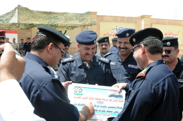 CONTINGENCY OPERATING BASE SPEICHER, TIKRIT, Iraq -Senior Iraqi Police leadership read a plaque that was presented to them during the district validation ceremony at the Tikrit District Headquarters, May 19.Tikrit is the first district in Salah ad-Din province to become validated to operate independently.