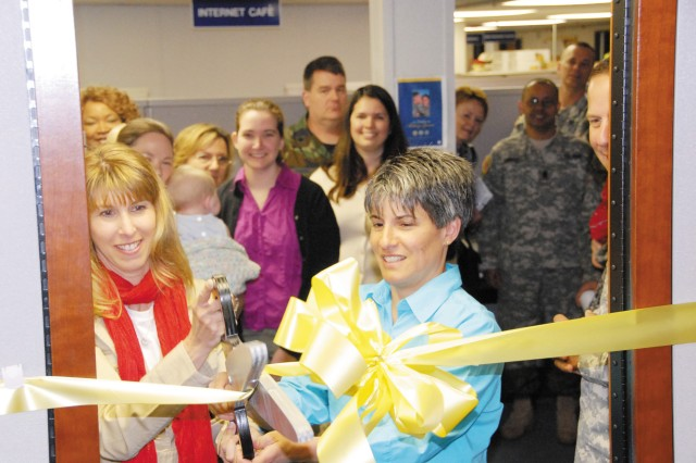 Liz Blakely, Family Readiness Group lead coordinator, left, and Lisa Snow, a FRG advisor and wife of 20th SUPCOM (CBRNE) commander Brig. Gen. Jeffrey J. Snow, cut the yellow ribbon at the grand opening of the CBRNE Yellow Ribbon Room April 21.