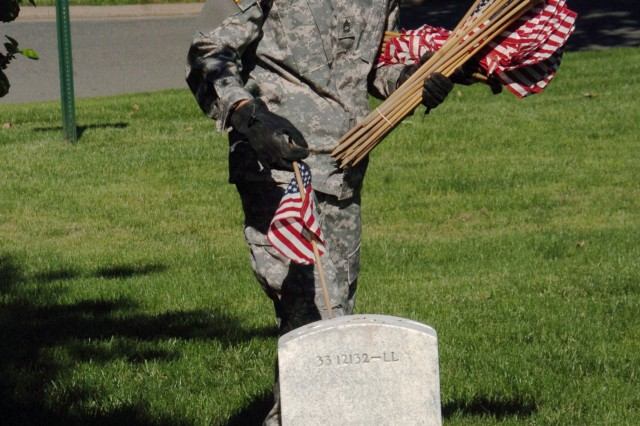 Sgt. 1st Class Ismael de los Santos, a senior fife insturmentalist with The Old Guard Fife and Drum Corps, places a flag at a grave in Section 33 of Arlington National Cemetery during Flags In.  Since 1948, The Old Guard has been participating in Flags In.
