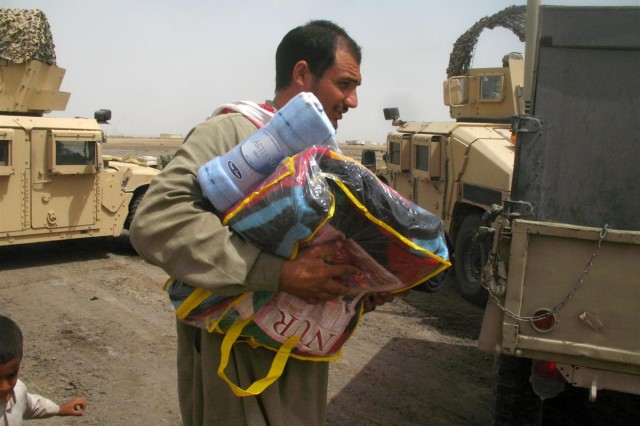 """At each stop of """"Bedouin Express,"""" civil military operations team members from the 167th Combat Sustainment Support Battalion and the 287th Sust. Brigade distributed water, blankets, clothes and toys to Bedouin families in Dhi Qar province,"""