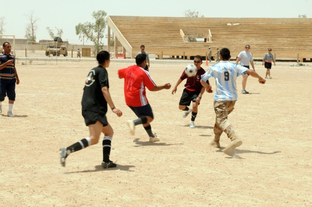 CONTINGENCY OPERATING BASE SPEICHER, TIKRIT, Iraq -Iraqi Soldiers of 4th Motor Transport Regiment, 4th Iraqi Army Division play alongside Soldiers of 325th Brigade Support Battalion, 3rd Infantry Brigade Combat Team, 25th Infantry Division in a competitive game of soccer during a combined sports day designed to honor fallen U.S. Soldiers on Memorial Day, May 25.