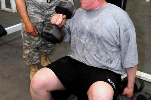 Sgt. 1st Class Luis R. Laluz supervises Sgt. Joshua S. Moak during a workout in a gym at Al Asad Air Base, Iraq, May 4. Moak lost 40 pounds in two and a half months in Lauz's physical fitness program.