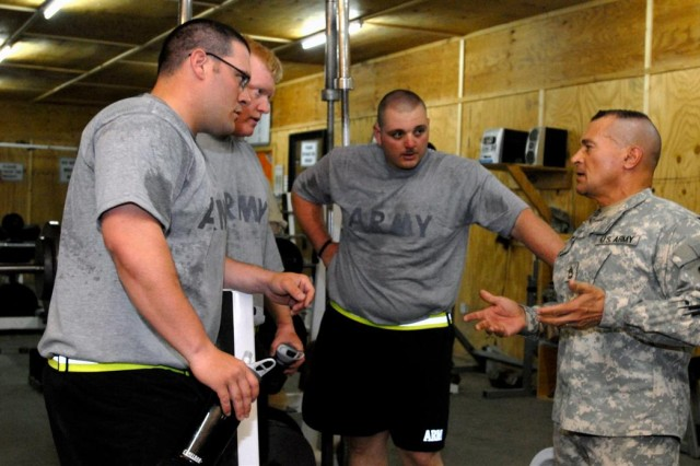 Sgt. 1st Class Luis R. Laluz, far right, of Staten Island, N.Y., offers Soldiers weight lifting tips in a gym at Al Asad Air Base, Iraq, May 4. An Amateur bodybuilder and former bodybuilding champion, Laluz started a physical fitness program for Soldiers in his unit, the 321st Sustainment Brigade.