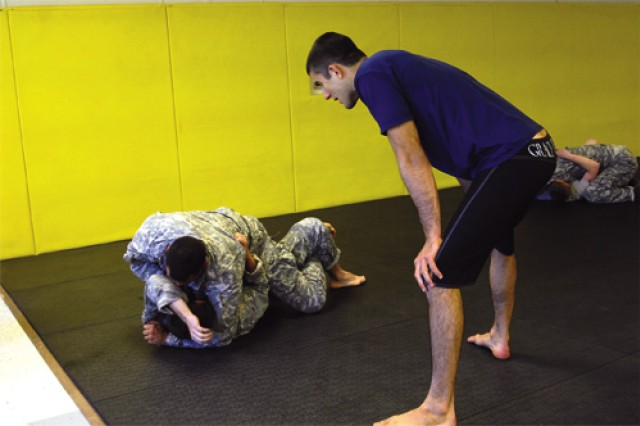 Rener Gracie talks Sgt. Chris Kratsas, Dive Company, 6th Transportation Battalion, 7th Sust. Bde., through a submission hold on fellow diver Staff Sgt. Ross Henderson.