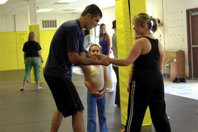 Rener Gracie tests a participant's escape technique during a Women and Children's Self-defense Class at the dojo May 21. The class, attended by nine women, one teen and two children, included techniques for escaping holds of would-be attackers and kidnappers and other means of protection.