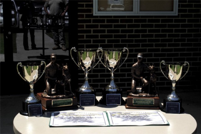 The trophies awarded to the 221st MP Det. teams include (from left) Scouting 3rd place team award, Top Kennel unit award, Top Kennel trophy, 1st place Endurance Challenge award, and third place trophy for Explosives Ordnance Detection.