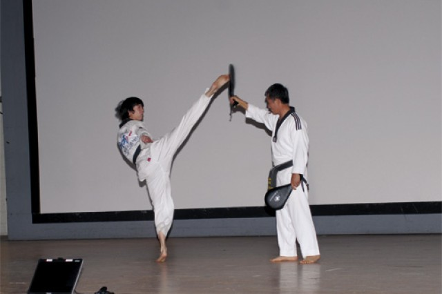 Roland Gilroy, left, and Grand Master Pyong Ko of World Martial Arts demonstrate martial arts self-defense moves during the ceremony.