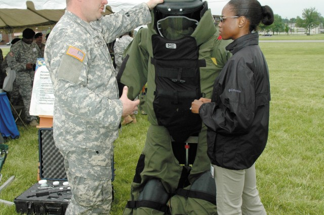 Staff Sgt. Harry Thompson, an explosive ordnance technician with the 20th Support Command (CBRNE), left, shows the features of an EOD protective suit to Adrienne Howard, an education researcher with the U.S. Army Medical Research Institute of Chemical Defense.