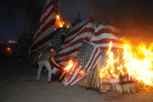 A member of the Vietnam Veterans of America Central New York Chapter 103 lights the 18th Annual Watchfire at the New York State Fairgrounds on Sunday to properly dispose of American flags.