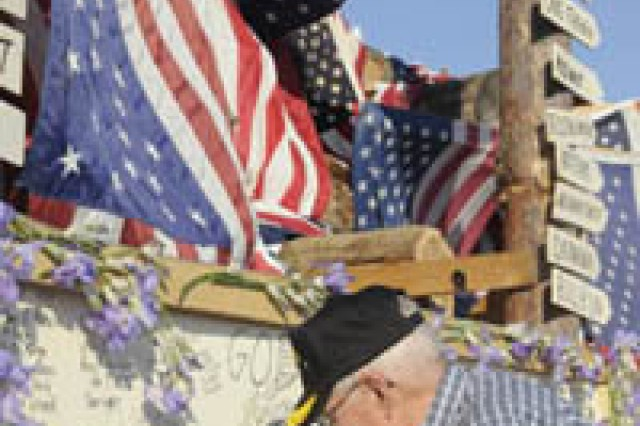"""Retired Army Lt. Col. Daniel Marvin writes """"We owe our freedom to those who serve the USA flag"""" at Sunday's Watchfire at the New York State Fairgrounds, Syracuse."""
