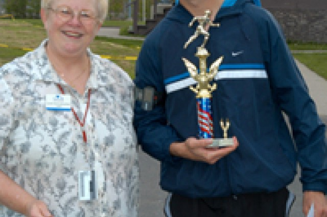 Lynn Schwabenthal, acting FMWR director, congratulates Sgt. Chris Lawrence on finishing first in the Fort Drum Qualifier for the Army ten-Miler with a time of 34.16