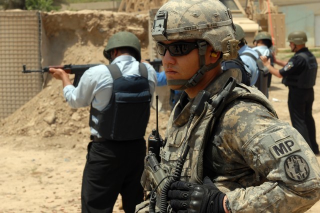 BAGHDAD - Sgt. Brandon Roque, a police transition team chief assigned to the 300th Military Police Company, 91st MP Battalion, 8th MP Brigade, watches as the Iraqi Police he trained administer a firing range at Joint Security Station Shuleik, here, May 21. According to the San Diego native, the MPs have graduated about 80 IPs during four Iraqi Primary Leadership Development Courses. The firing range has been the culminating event for all of the rotations.